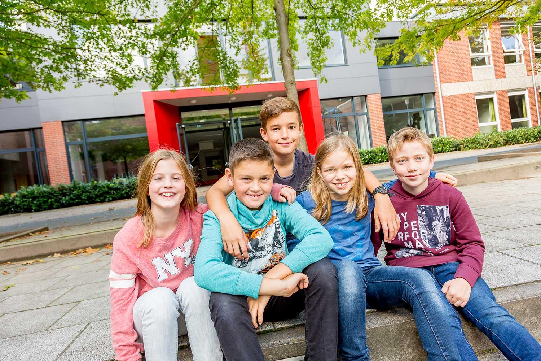 Schüler sitzen vor einem Schulgebäude